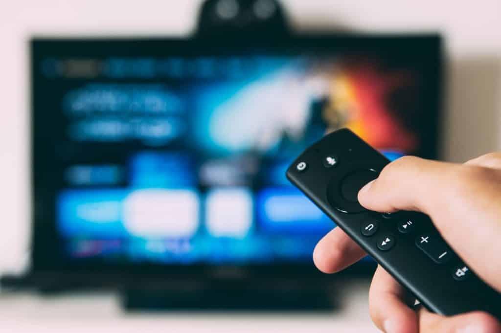 Пульт от телевизора в руках человека